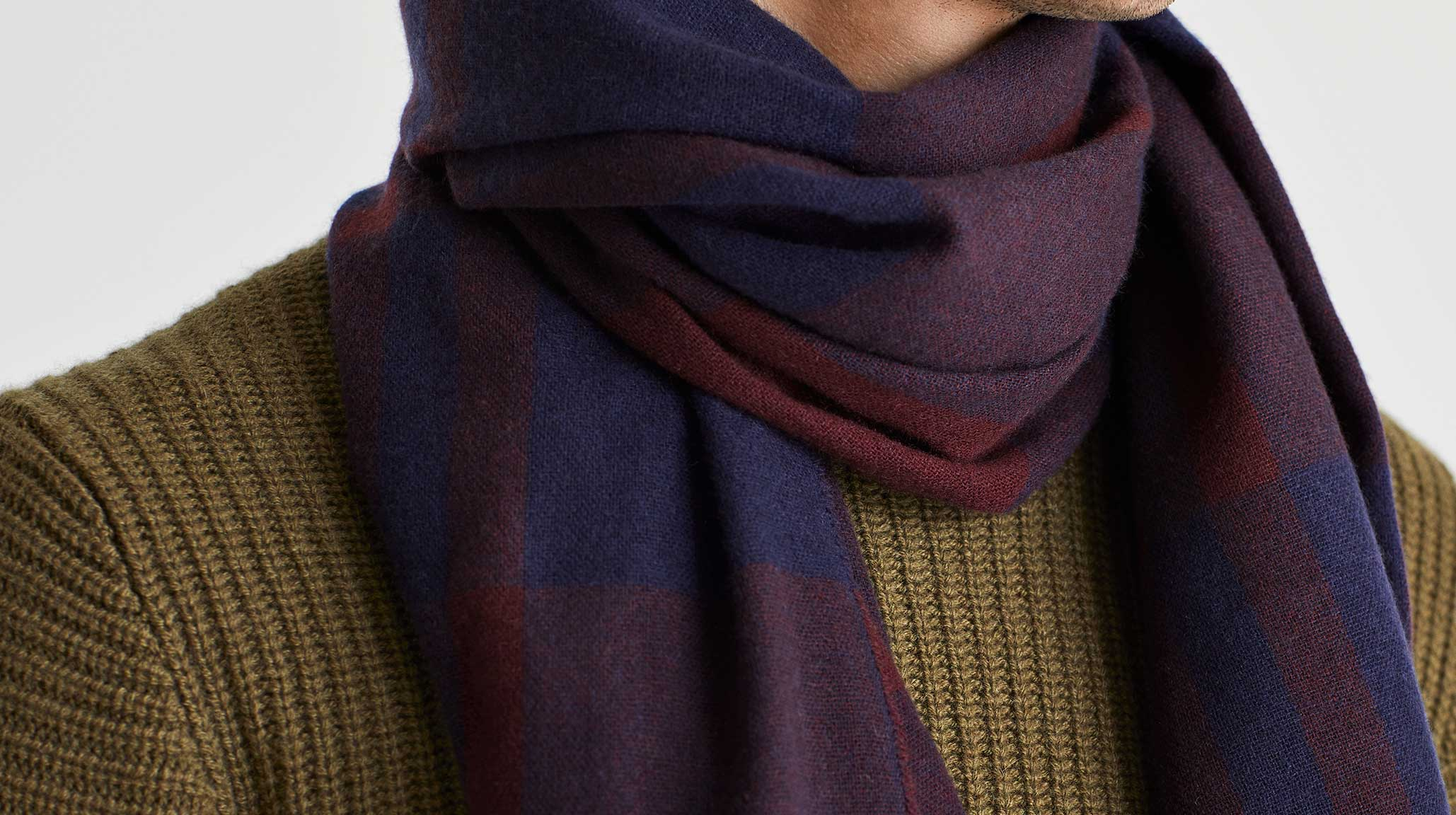 Man wearing green ribbed cashmere jumper and purple cashmere scarf