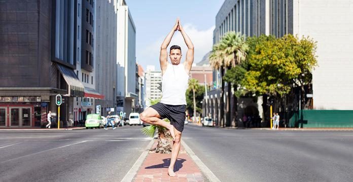 Yoga Pose auf einer Verkehrsinsel einer belebten Straße