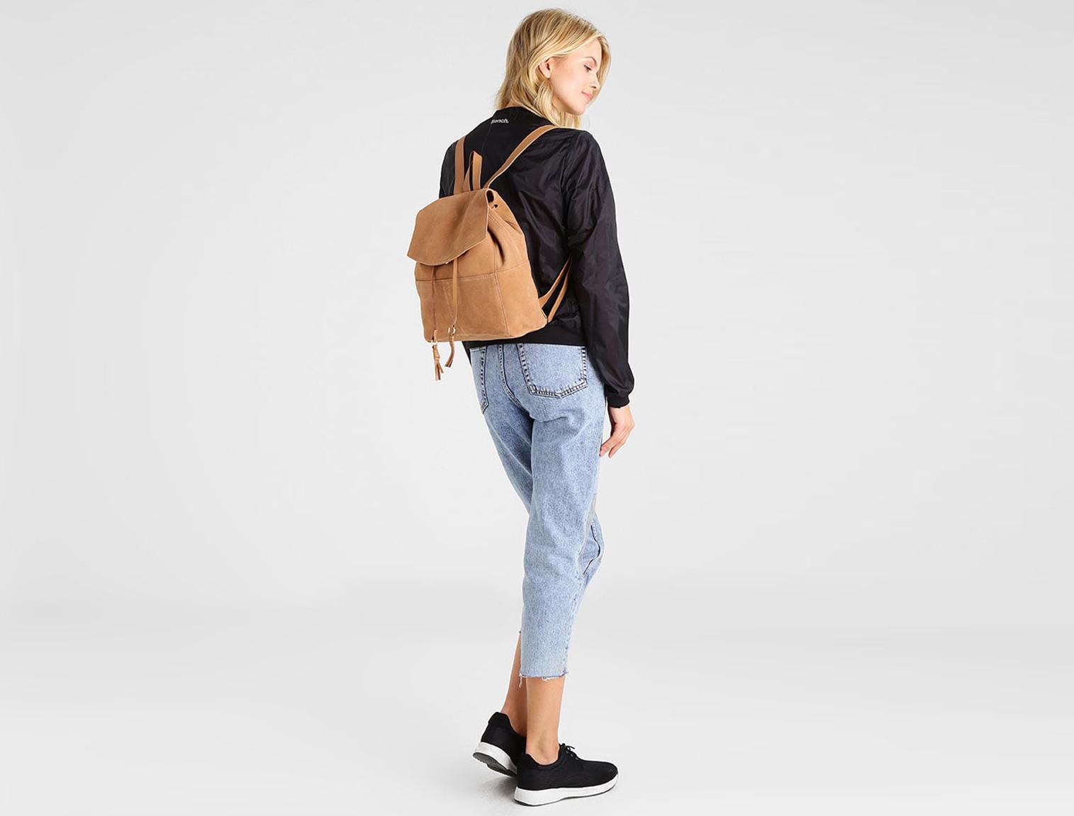 Mujer con mochila de piel marrón